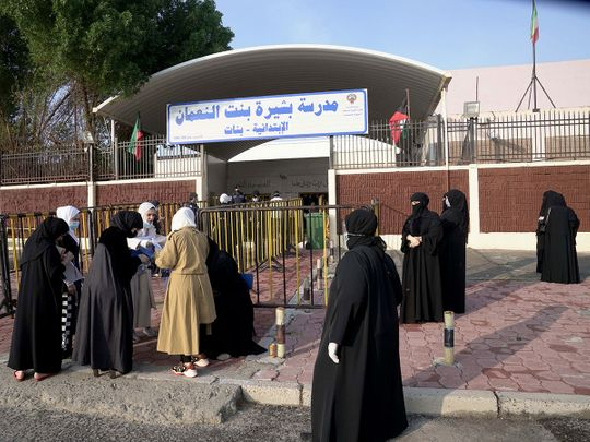 Kuwaiti women gather at the entrance of a polling station
