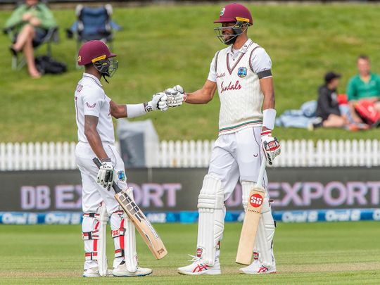 West Indies' Jermaine Blackwood  (L) and Roston Chase touch gloves during the third day of the first Test cricket match between New Zealand and West Indies