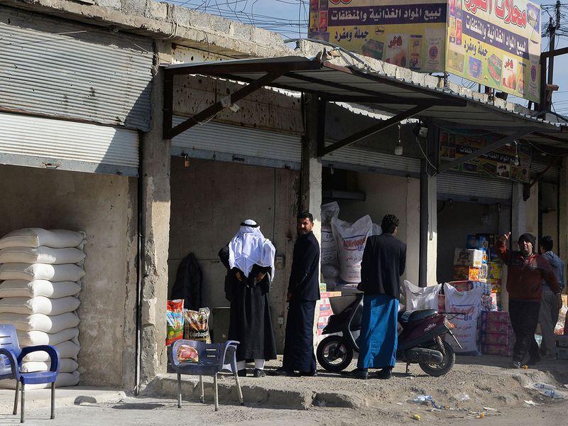 Iraqis buy goods at a shop at the