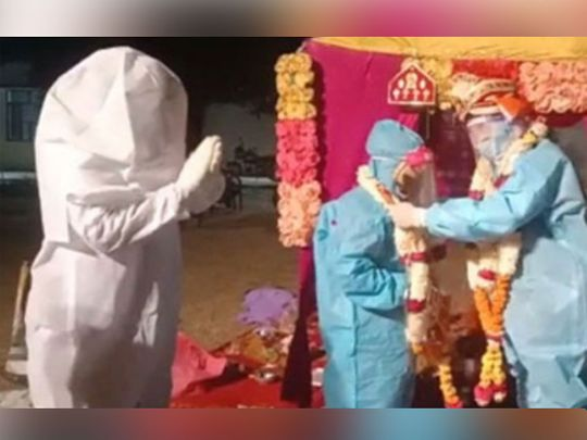 Couple ties knot in PPE kits after bride tests positive for COVID-19