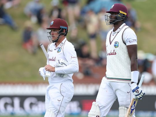 West Indies batsmen Jason Holder (R) and Joshua Da Silva leave the field as bad light stops play on day three of the second cricket Test match between New Zealand and the West Indies