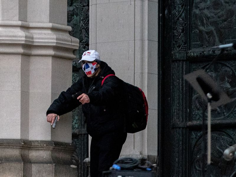 A man wearing a protective mask points his guns outside the Cathedral Church of St. John the Divine in the Manhattan borough of New York City, New York, U.S., December 13, 2020.