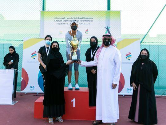 Riya Matharoo of India receives the Sharjah Women's Tennis Championships winner's trophy from Issa Hilal Al Hazami and Nada Askar Al Naqbi