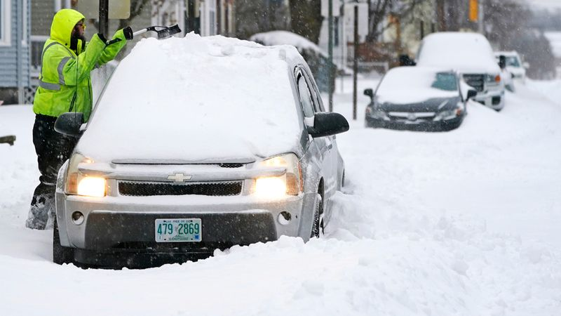 A man clears snow from his car, in Manchester, New Hampshire.