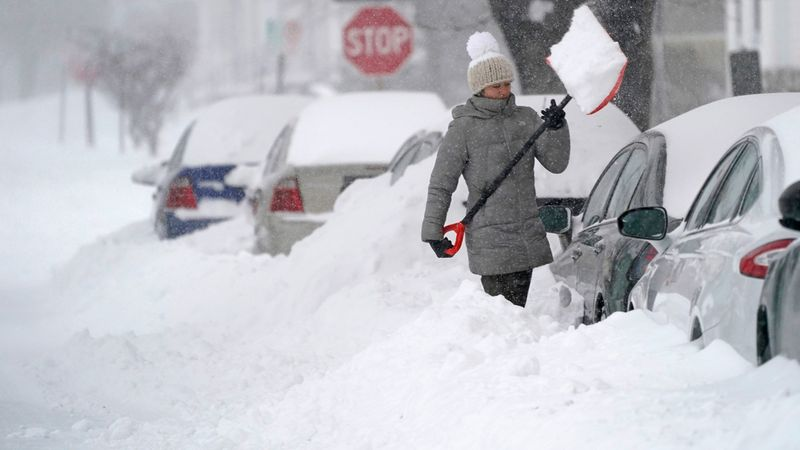 A woman tosses a shovel full of snow while digging out her car, in Manchester, New Hampshire.