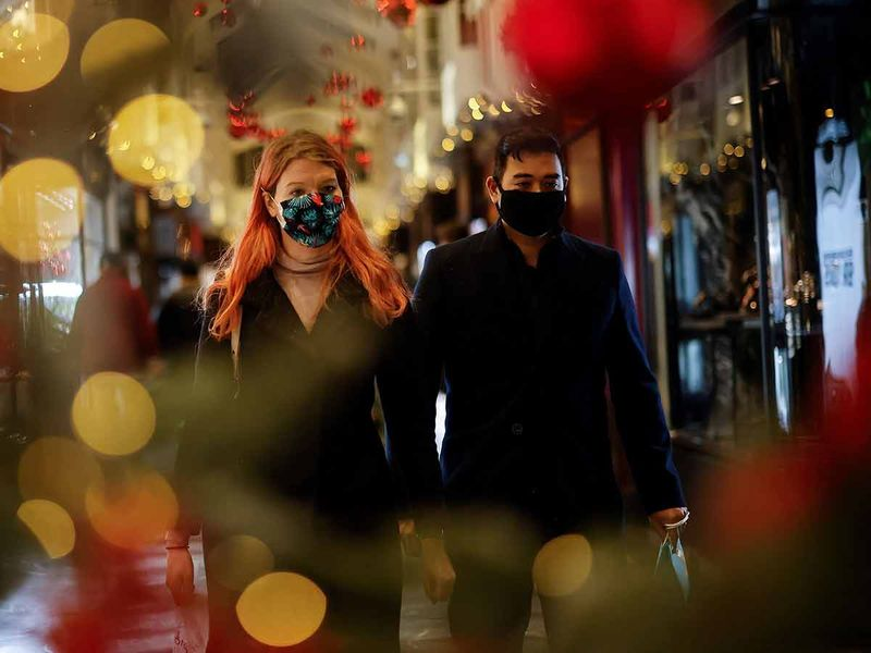 Shoppers, some wearing a face mask or covering due to the COVID-19 pandemic, look at shop window displays inside a christmas-themed Burlington Arcade in London on December 19, 2020.