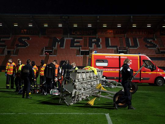 Medical staff and firemen try to rescue the groundskeeper at Lorient's stadium