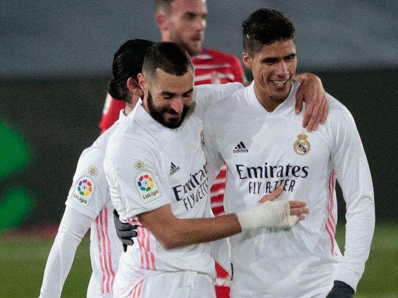 Real Madrid's Raphael Varane, right, celebrates the win over Granada with Karim Benzema