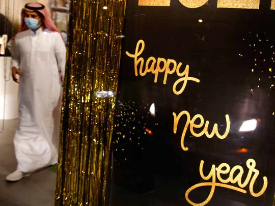 A man wearing a mask to protect from the coronavirus leaves a gift shop decorated for the New Year in Jiddah, Saudi Arabia, Friday, Dec. 25, 2020.