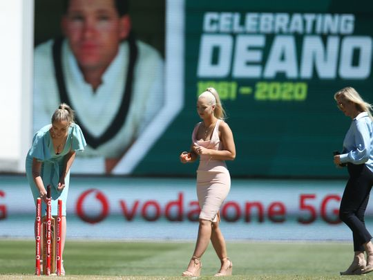Daughters of former Australian cricketer Dean Jones, Phoebe, left, and Augusta walk with their mother, Jane, right, for a tribute for the late batsman during the tea break on day one of the Boxing Day cricket test between India and Australia at Melbourne Cricket Ground