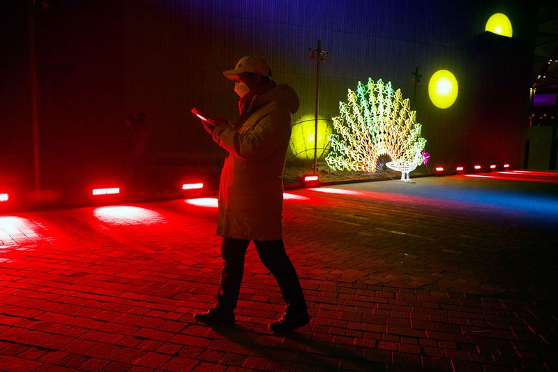 A man walks near a light sculpture before a New Year's eve countdown event at the 2022 Beijing Winter Olympic headquarters in Bejiing.