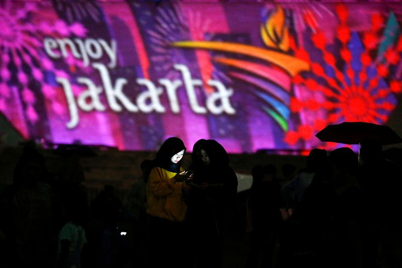 A woman uses a phone as National Monument (Monas) is illuminated by video mapping during New Year's Eve celebrations in Jakarta, Indonesia.