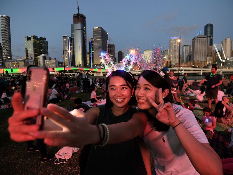 Girls take a selfie as they wait to watch the New Year's Eve fireworks at South Bank in Brisbane, Australia.
