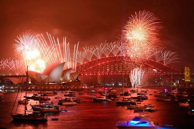 New Year's Eve fireworks erupt over Sydney's iconic Harbour Bridge and Opera House (L) during the fireworks show.