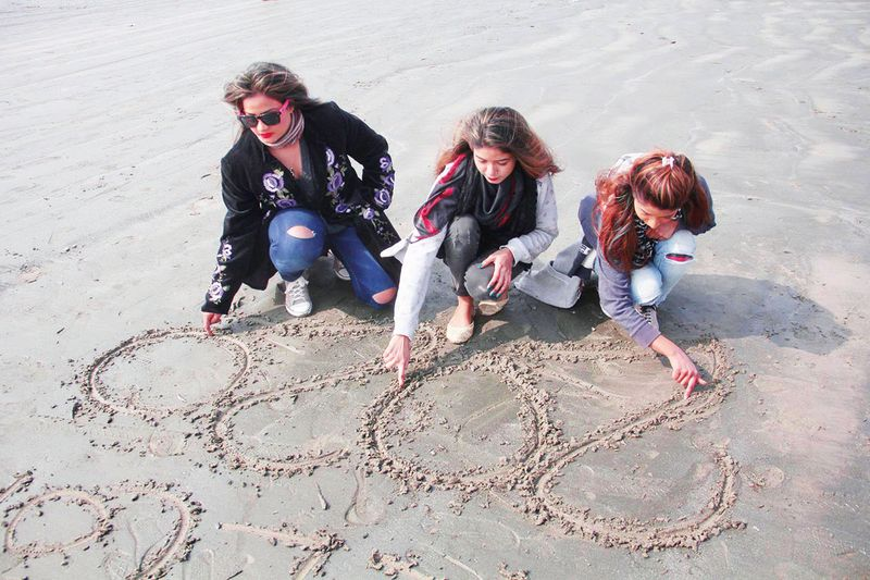 Pakistani girls are busy in writing of Happy New Year 2020 at the beach of Sea View ahead of Year New Year celebrations in Karachi.