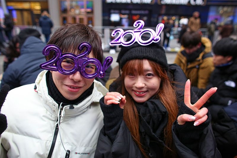People from Japan gesture as they await before the New Years eve celebration in Times Square in New York City.