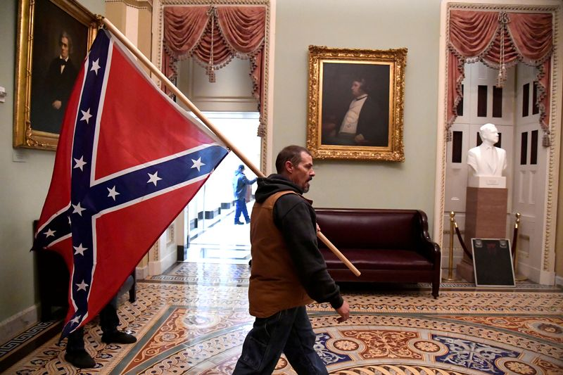 A supporter of President Donald Trump carries a Confederate battle flag on the second floor of the U.S. Capitol near the entrance to the Senate after breaching security defenses, in Washington.