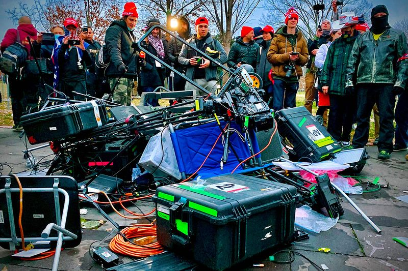 Supporters of US President Donald Trump stand next to media equipment they destroyed during protest outside the Capitol in Washington, DC. - Demonstrators breeched security and entered the Capitol as Congress debated the a 2020 presidential election Electoral Vote Certification.