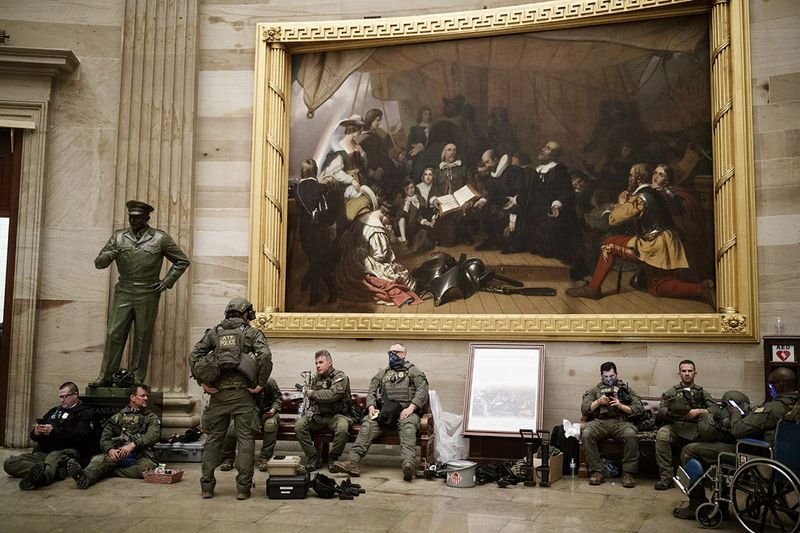 Members of law enforcement rest in the U.S. Capitol in Washington D.C., U.S., on Wednesday.  The House and Senate resumed a politically charged debate over the legitimacy of the presidential election hours after a pro-Trump mob stormed the U.S. Capitol and drove lawmakers from their chambers.