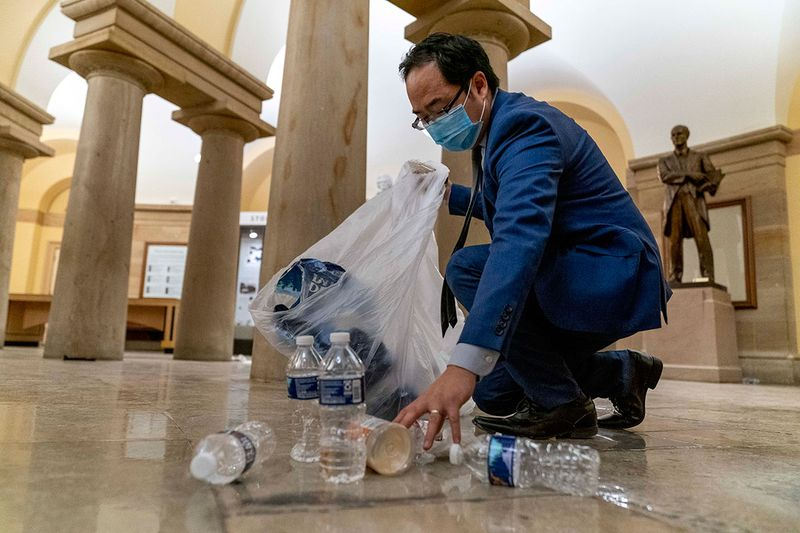 Rep. Andy Kim, D-N.J., cleans up debris and trash strewn across the floor in the early morning hours of Thursday, Jan. 7, 2021, after protesters stormed the Capitol in Washington, on Wednesday.
