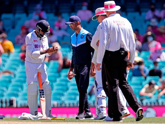 India's Ravindra Jadeja (L) holds his hand after he was hit by the ball on the third day of the third cricket Test match between Australia and India at the Sydney Cricket Ground