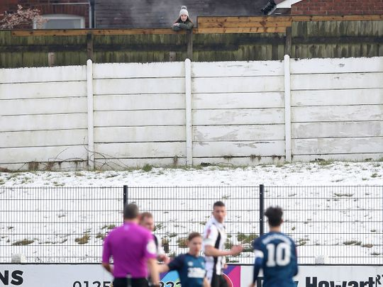A spectator watches the game from behind a fence, during the English FA Cup third round match between Chorley and Derby County, at Victory Park in Chorley
