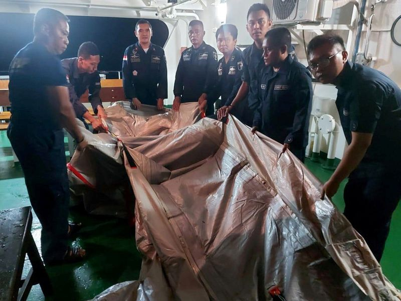Officers of an Indonesian Coast and Sea Guard (KPLP) patrol ship hold suspected remains of an emergency ladder of the Sriwijaya Air plane flight SJ182