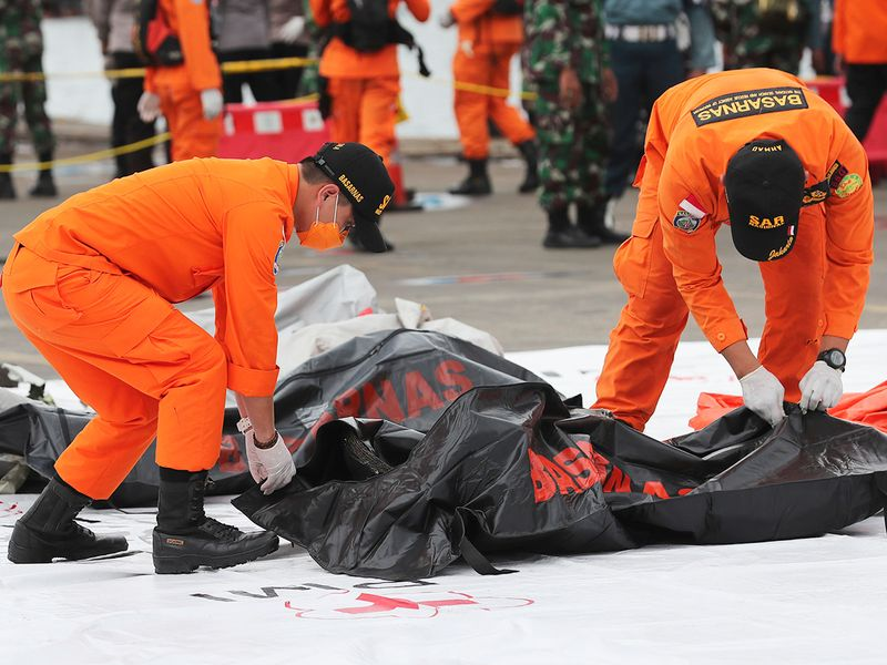Rescuers carry a body bag