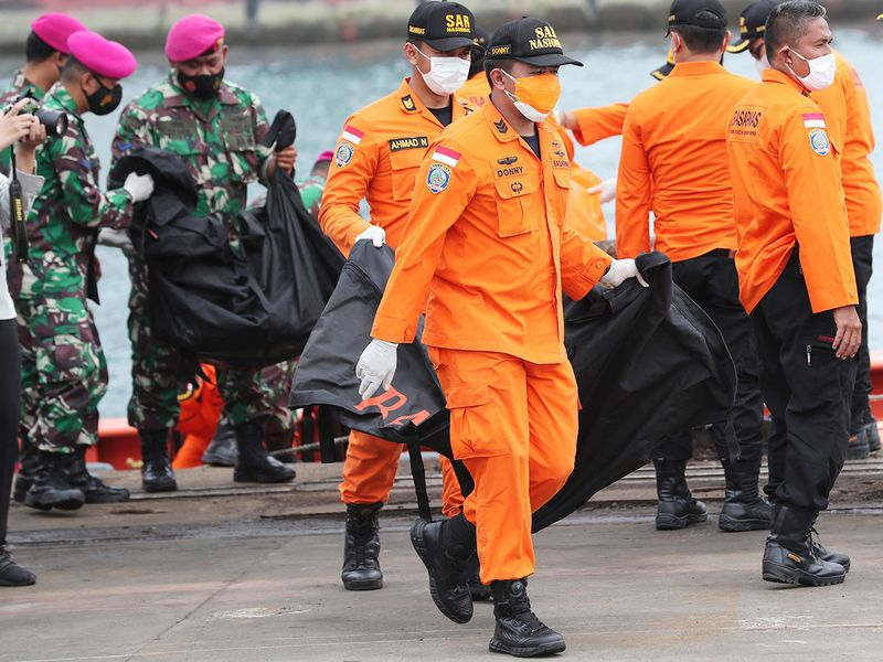 Rescuers carry body bags