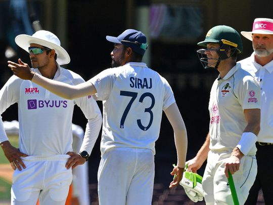 India's Mohammed Siraj (C) gestures next to Australia's captain Tim Paine (2R) as the game was halted after allegedly some remarks were made by the spectators on the fourth day of the third cricket Test match between Australia and India at the Sydney Cricket Ground