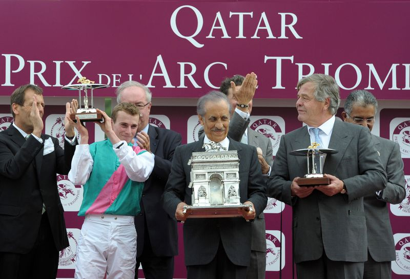 Prince Khalid bin Abdullah of Saudi Arabia, right, owner of Workforce, ridden by jockey Ryan Lee Moore of Great Britain, left, celebrate with the trophy after winning the Prix de l'Arc de Triomphe, Europe's premier middle-distance horse race, in 2010.