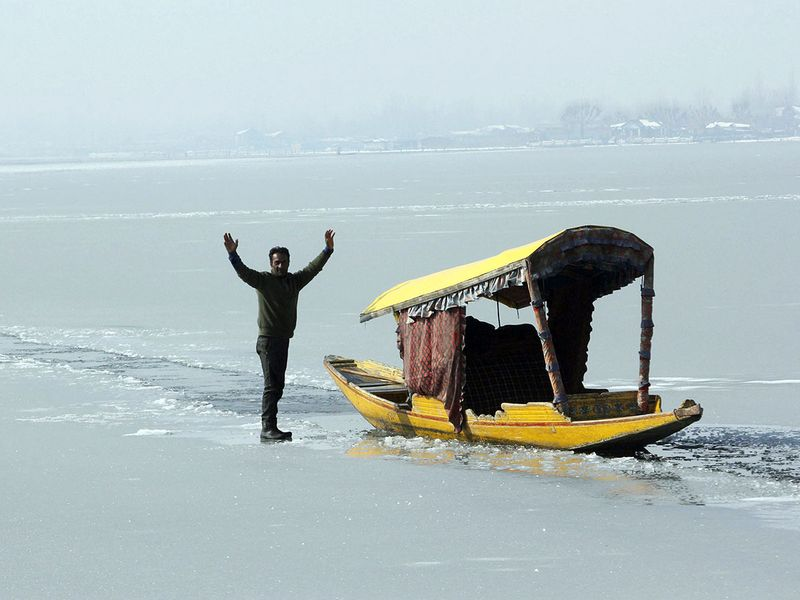 A boatman enjoys on frozen ice layer waters of a Dal lake in Srinagar.