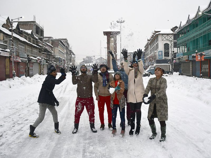 Tourists enjoy at city center Lalchowk during fresh snowfall, in Srinagar.