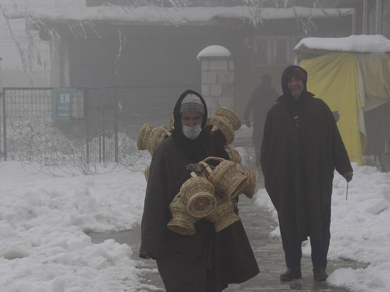 A vendor sells firepots during a cold day, in Srinagar on Thursday.