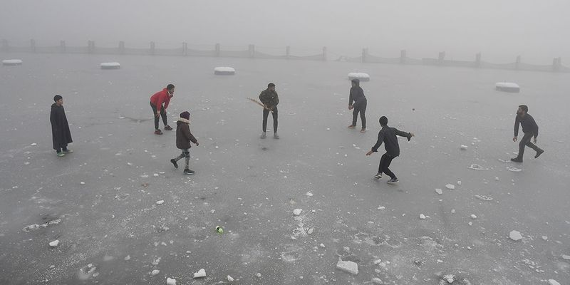 Boys playing cricket on a frozen Dal Lake, in Srinagar