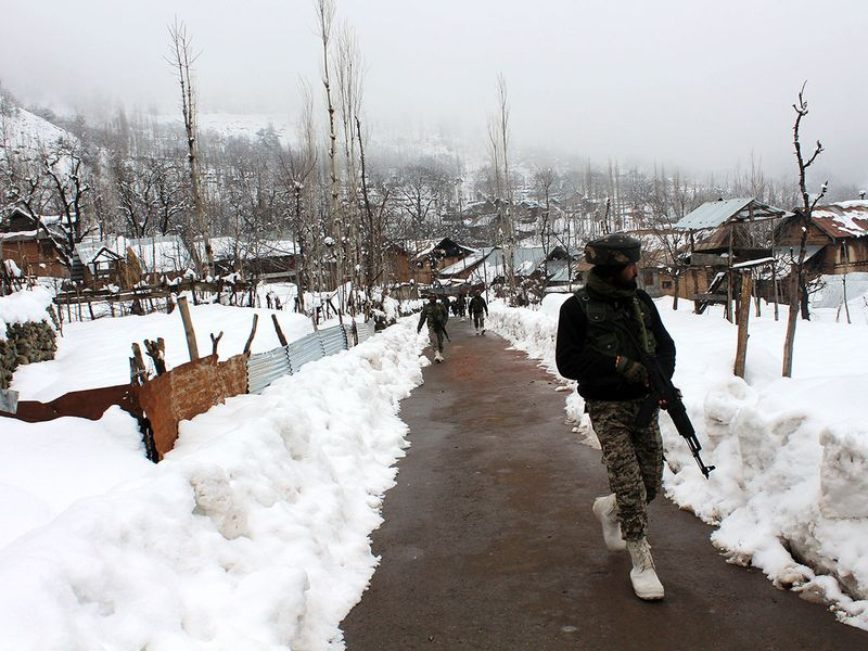 CRPF personnel patrolling at a snow-covered area, in Pulwama district on Thursday.