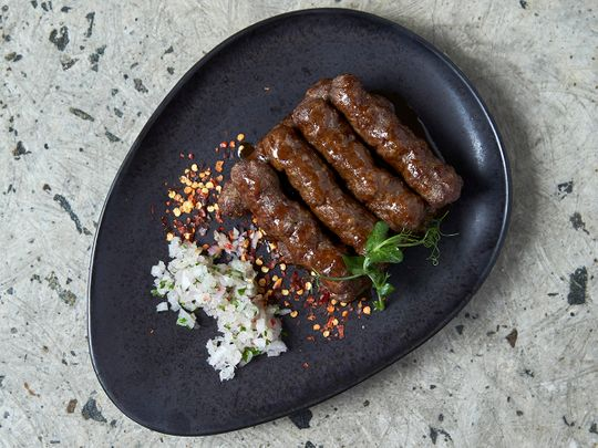 Cevapi's delicious served with some sliced onions and flatbread