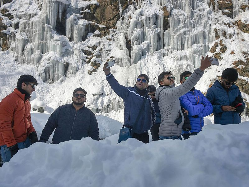 Tangmarg: Tourists take selfies in the back drop of a frozen waterfall at Tangmarg, in Baramulla district of north Kashmir, Thursday, Jan. 14, 2021.