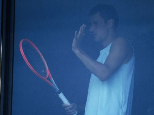 Bernard Tomic is pictured at his hotel room window