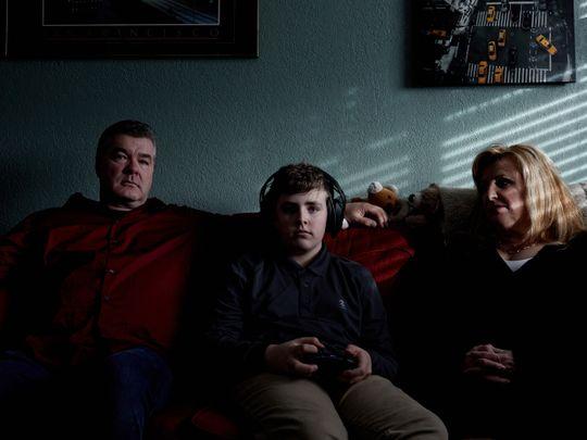 John and Cathleen Reichert watch as their son, James, plays video games