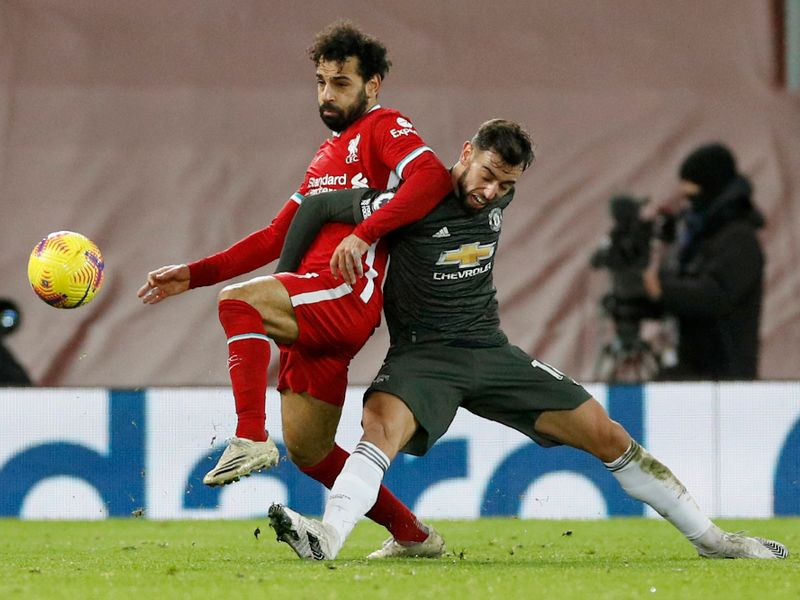 Manchester United's Bruno Fernandes fights for the ball with Liverpool's Mohamed Salah.
