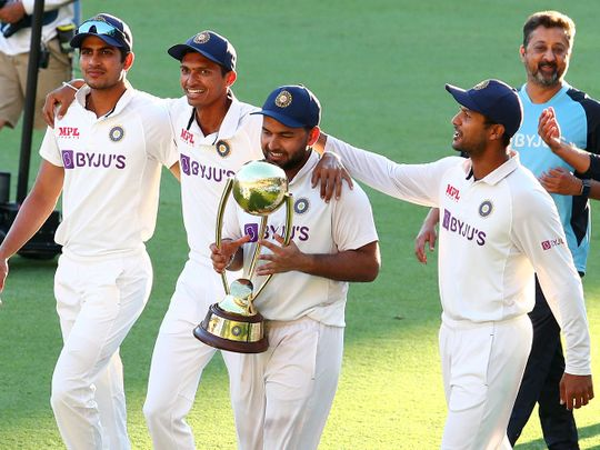 India's Rishabh Pant carries the Border-Gavaskar Trophy as he celebrates with his teammates after defeating Australia by three wickets on the final day of the fourth cricket test at the Gabba, Brisbane, Australia.