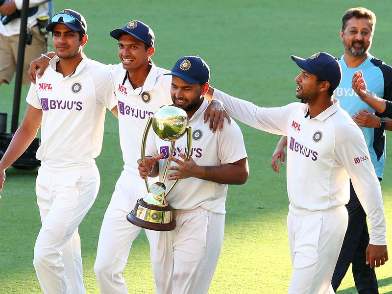 India's Rishabh Pant carries the trophy as he celebrates with his teammates after defeating Australia by three wickets on the final day of the fourth cricket test at the Gabba, Brisbane, Australia, Tuesday, Jan. 19, 2021.India won the four test series 2-1.