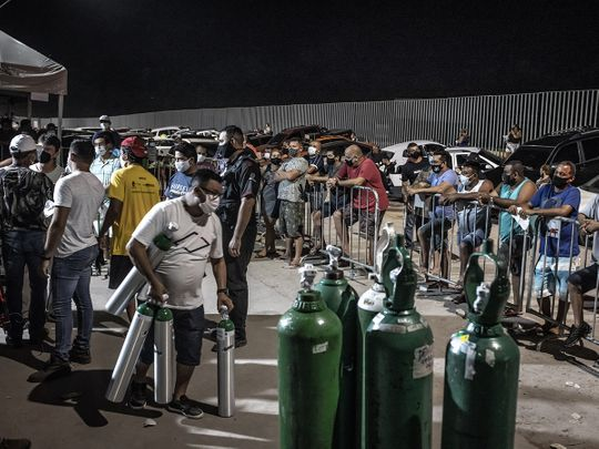 People wearing protective masks wait in line to refill oxygen tanks in Manaus.
