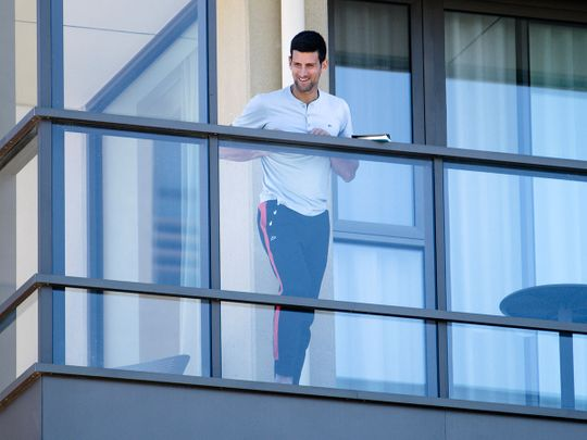 Serbia's Novak Djokovic stands on the balcony at his accommodation in Adelaide, Australia.