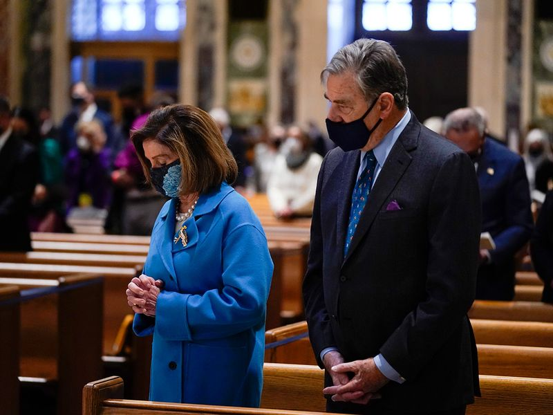 House Speaker Nancy Pelosi, left, and her husband Paul Pelosi attend Mass at the Cathedral of St. Matthew the Apostle during Inauguration Day ceremonies, in Washington.