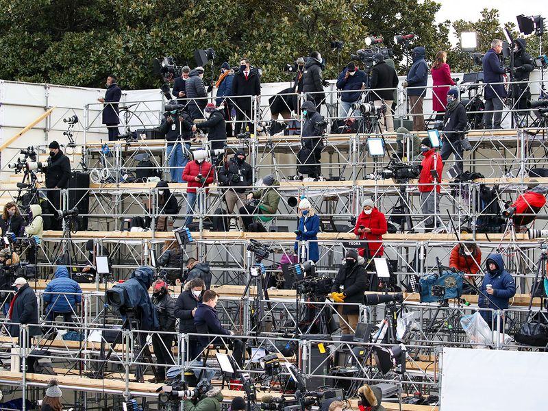 Members of the media work on the social-distanced riser at the inauguration of President-elect Joe Biden on the West Front of the US Capitol in Washington, DC.