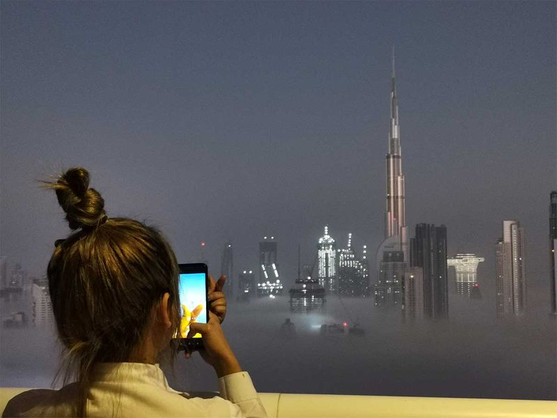 A resident takes pictures of the fog-covered Dubai skyline with Burj Khalifa in the background, from Damac Towers.