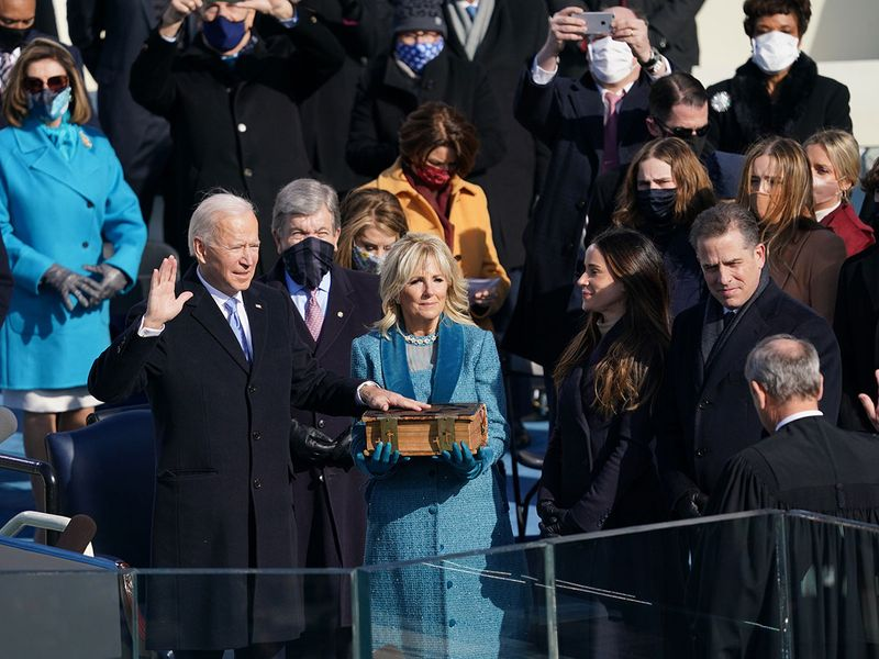 "Joe Biden is sworn in as the 46th President of the United States at the Capitol in Washington on Wednesday, Jan. 20, 2021, as his wife Jill Biden holds a bible. The theme of the Biden inauguration was ""America United,"" and the color of the day seemed to be purple — the shade that bridges the divide by bringing both colors together (not to mention one of the original signature colors of the suffragists, whose dreams are now being realized with the first woman vice president)"