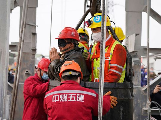 One of twenty-two Chinese miners wearing a black patch is saved from hundreds of metres underground, where they had been trapped for two weeks after a gold mine explosion in Qixia, in eastern China's Shandong province.